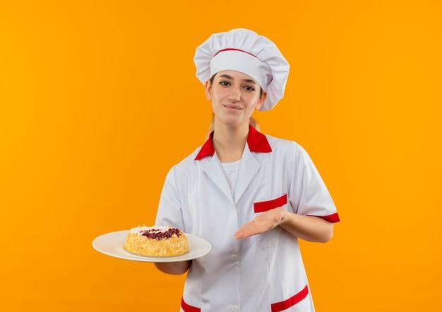 Erfreut junge hübsche köchin in der kochuniform, die mit der hand auf teller des kuchens hält und auf orange raum lokalisiert zeigt