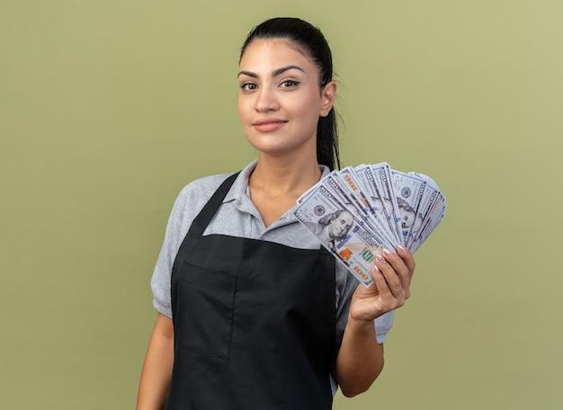 Erfreut junge kaukasische friseurin in uniform, die geld auf olivgrüner wand isoliert