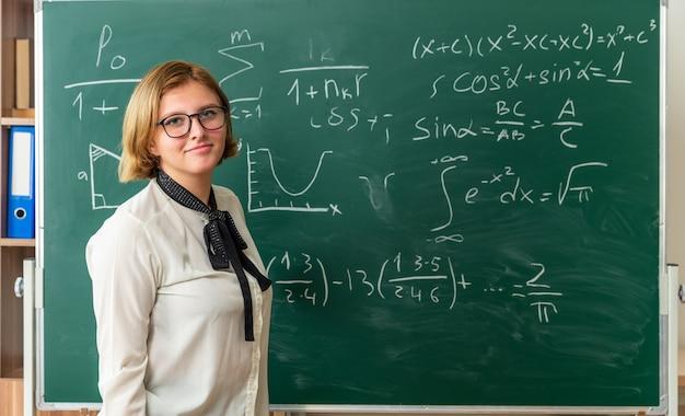Erfreut junge lehrerin mit brille, die vor der tafel im klassenzimmer steht standing