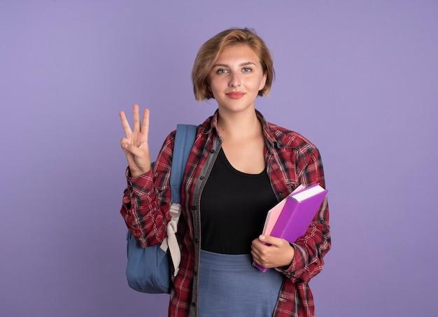Erfreut junge slawische studentin mit rucksack hält buch und notizbuch gesten drei mit den fingern