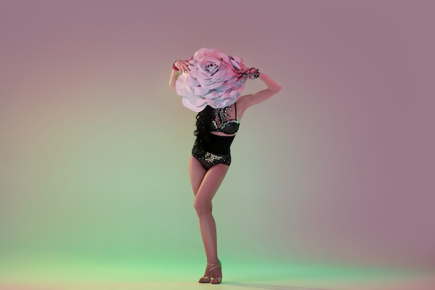 Erfreut. junge tänzerin mit riesigen blumenhüten im neonlicht an der wand mit farbverlauf. anmutiges modell, frau tanzen, posieren. konzept von karneval, schönheit, bewegung, blühen, frühlingsmode.