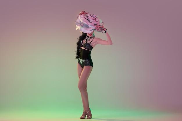 Erfreut. junge tänzerin mit riesigen blumenhüten im neonlicht an der wand mit farbverlauf.