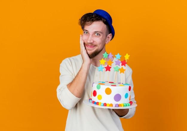 Erfreut jungen gutaussehenden slawischen party-typ, der partyhut hält, der geburtstagstorte mit sternen betrachtet, die kamera berühren gesicht lokalisiert auf orange hintergrund mit kopienraum betrachten