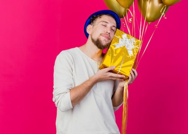 Erfreut jungen gutaussehenden slawischen party-typ, der partyhut hält, der luftballons hält und gesicht mit geschenkbox mit geschlossenen augen berührt, die auf purpurrotem hintergrund mit kopienraum lokalisiert werden