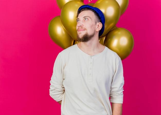 Erfreut jungen gutaussehenden slawischen party-typ, der partyhut hält, der luftballons hinter seinem rücken hält und seite betrachtet, die auf rosa wand mit kopienraum lokalisiert wird