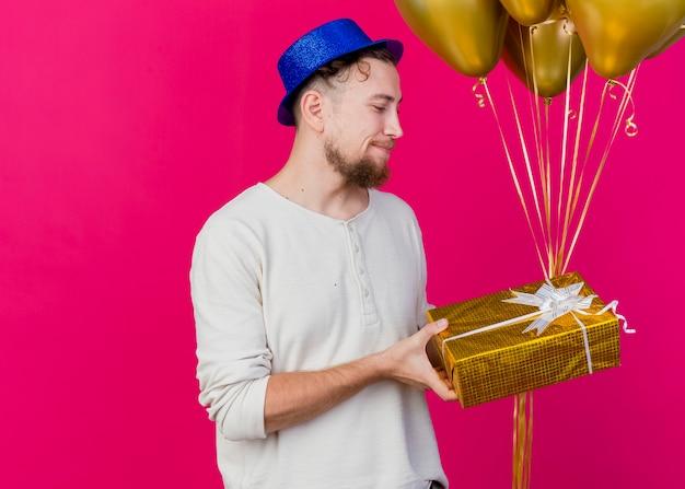 Erfreut jungen gutaussehenden slawischen party-typ, der partyhut hält, der luftballons und geschenkbox hält, die geschenkbox lokalisiert auf purpurrotem hintergrund mit kopienraum betrachtet