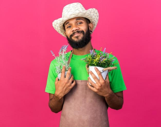 Erfreut junger afroamerikanischer gärtner mit gartenhut, der blumen im blumentopf hält