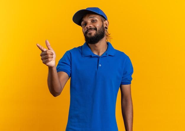 Erfreut junger afroamerikanischer lieferbote, der auf die seite zeigt, die auf einer orangefarbenen wand mit kopierraum isoliert ist?