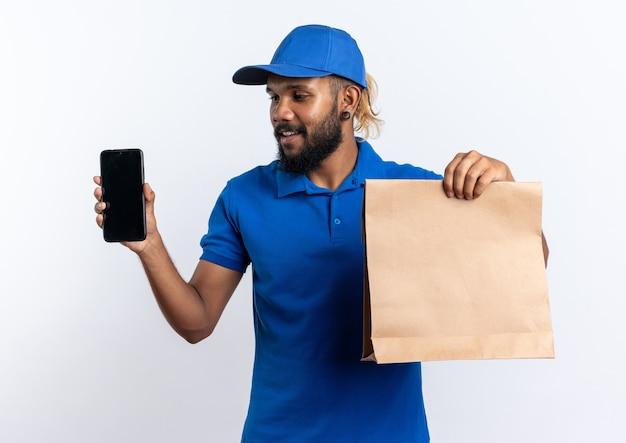 Erfreut junger afroamerikanischer lieferbote, der lebensmittelpaket und telefon isoliert auf weißem hintergrund mit kopienraum hält