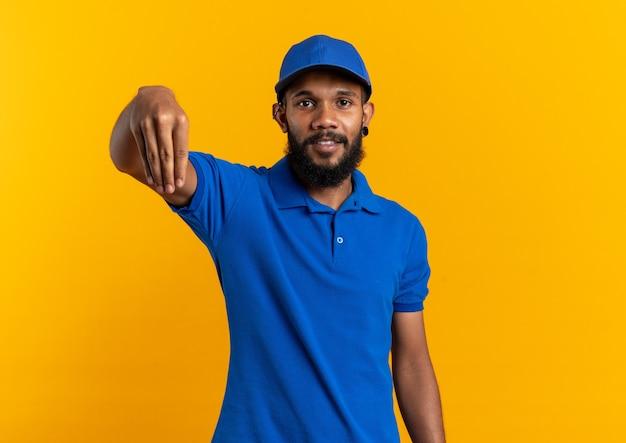 Erfreut junger afroamerikanischer lieferbote, der vorgibt, etwas isoliert auf orangefarbener wand mit kopierraum zu halten?