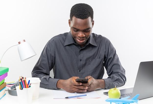 Erfreut junger afroamerikanischer student, der am schreibtisch mit schulwerkzeugen sitzt und das telefon hält und betrachtet