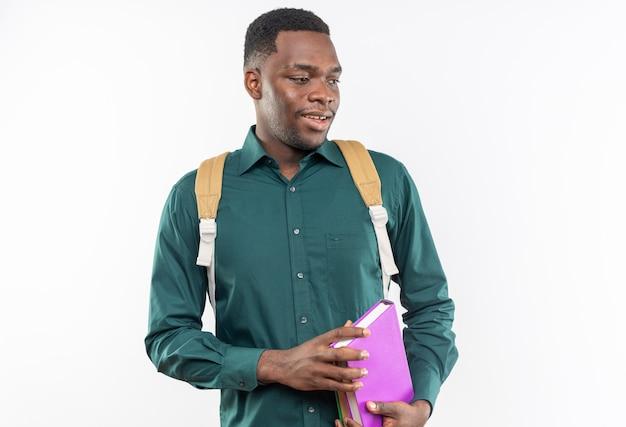 Erfreut junger afroamerikanischer student mit rucksack, der bücher hält und die seite isoliert auf weißer wand mit kopienraum betrachtet