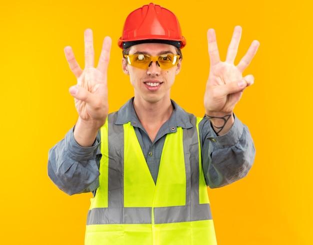 Erfreut junger baumeister in uniform mit brille, die drei zeigt