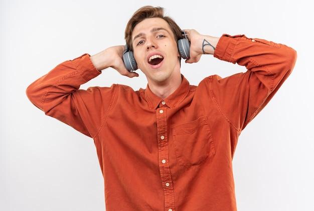 Erfreut junger gutaussehender kerl, der rotes hemd mit kopfhörern trägt