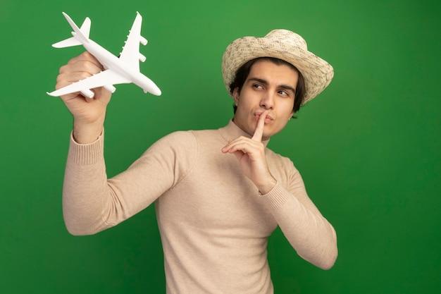 Erfreut junger, gutaussehender kerl mit hant, der ein spielzeugflugzeug anhebt und betrachtet, das stillegeste einzeln auf grüner wand zeigt