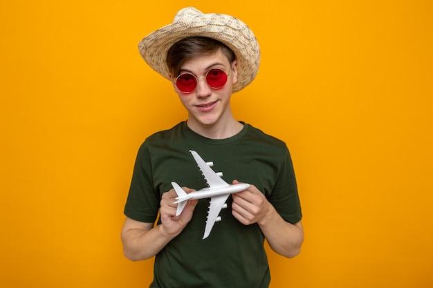 Erfreut junger gutaussehender kerl mit hut mit brille, der spielzeugflugzeug hält