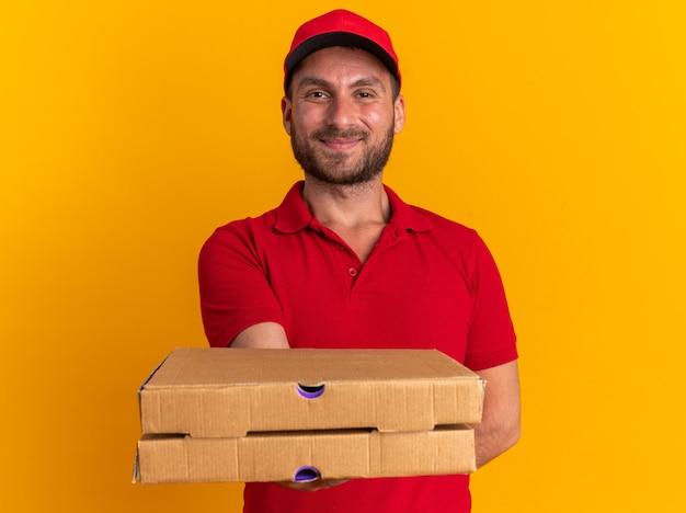 Erfreut junger kaukasischer lieferbote in roter uniform und mütze, die die hand hinter dem rücken hält und auf die kamera schaut, die pizzapakete in richtung kamera ausstreckt, isoliert auf oranger wand