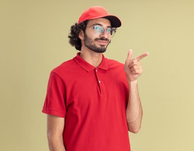 Erfreut junger kaukasischer lieferbote in roter uniform und mütze mit brille, die auf die seite zeigt