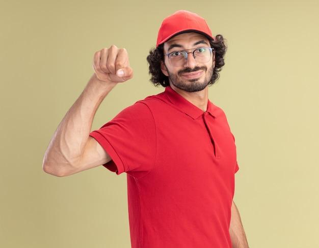 Erfreut junger kaukasischer lieferbote in roter uniform und mütze mit brille, die klopfgeste macht