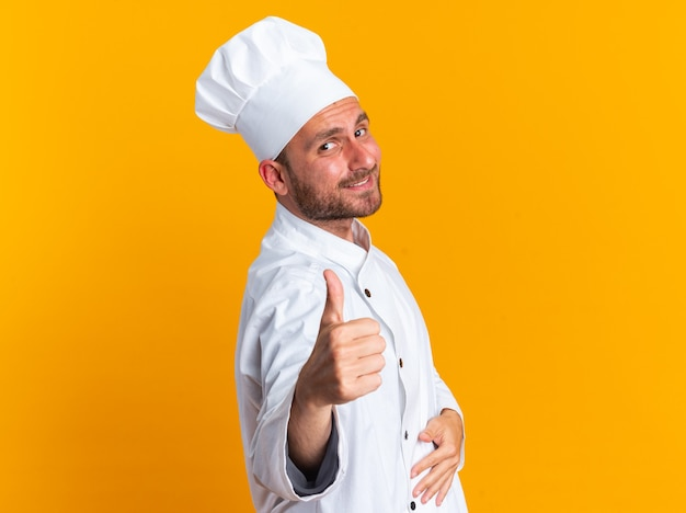 Erfreut junger kaukasischer männlicher koch in kochuniform und mütze, der in der profilansicht steht und die hand auf dem bauch hält und in die kamera schaut, die den daumen einzeln auf der orangefarbenen wand mit kopienraum zeigt