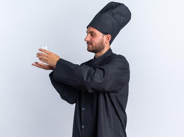 Erfreut junger kaukasischer männlicher koch in kochuniform und mütze, der in der profilansicht steht und versucht, ein glas wasser in seiner handfläche zu halten und es isoliert auf weißer wand zu betrachten