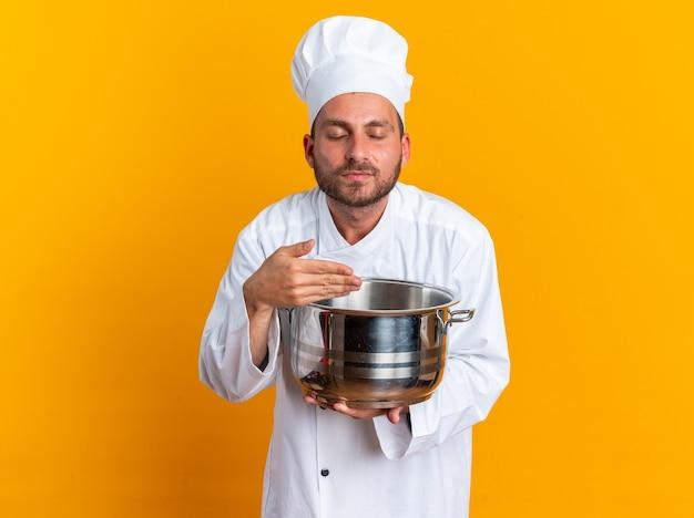 Erfreut junger kaukasischer männlicher koch in kochuniform und mütze mit topf, der die hand hält und mit geschlossenen augen schnüffelt