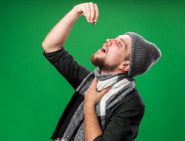 Erfreut junger kranker slawischer mann mit schal um den hals mit wintermütze, der medizinische pillen nimmt