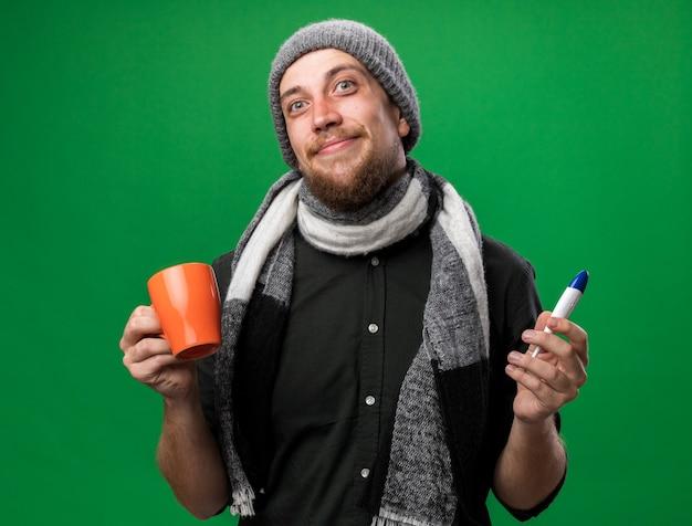 Erfreut junger kranker slawischer mann mit schal um den hals mit wintermütze, der thermometer und tasse isoliert auf grüner wand mit kopierraum hält
