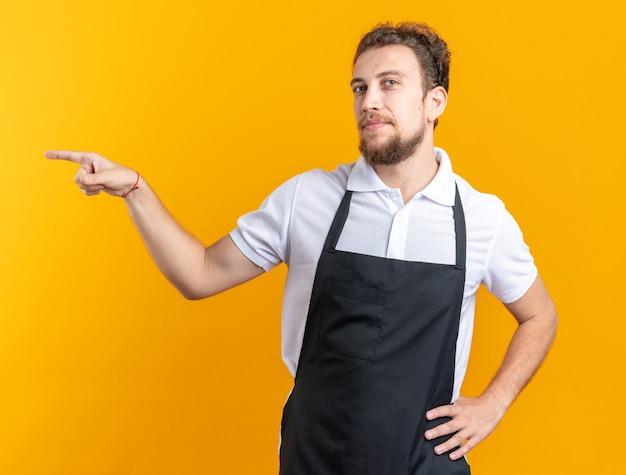 Erfreut junger männlicher friseur, der einheitliche punkte an der seite trägt und die hand auf die hüfte legt, isoliert auf gelber wand