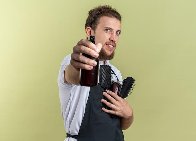 Erfreut junger männlicher friseur, der uniform trägt, die friseurwerkzeuge hält und die sprühflasche isoliert auf olivgrüner wand hält