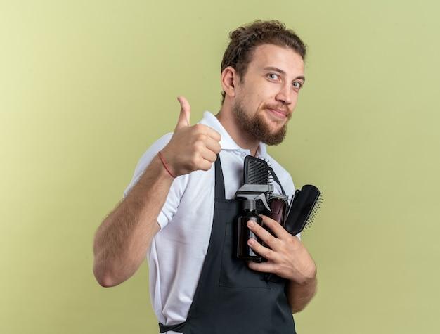 Erfreut junger männlicher friseur in uniform mit friseurwerkzeugen, der daumen nach oben isoliert auf olivgrüner wand zeigt