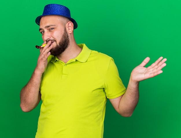 Erfreut junger mann mit blauem partyhut bläst partypfeife, die hand ausbreitet