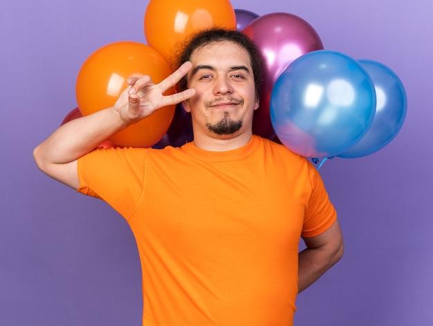 Erfreut junger mann mit orangefarbenem t-shirt, das vor ballons steht und friedensgeste zeigt, isoliert auf lila wand