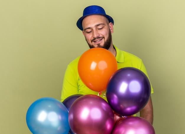 Erfreut, junger mann mit partyhut, der hinter ballons steht, isoliert auf olivgrüner wand, herunterschauen