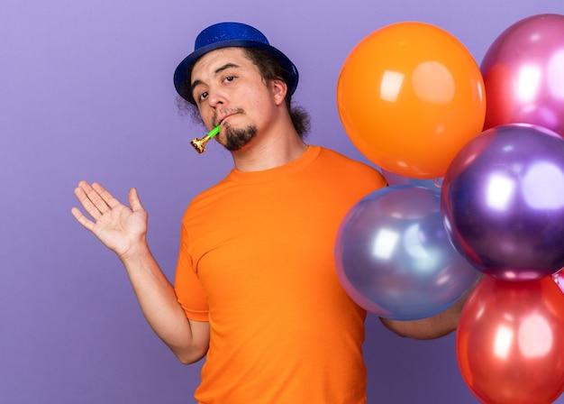 Erfreut junger mann mit partyhut, der luftballons hält und die partypfeife bläst, die hand isoliert auf lila wand ausbreitet