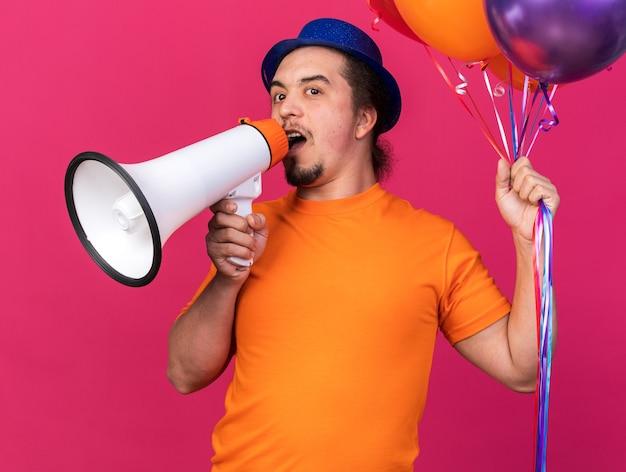 Erfreut junger mann mit partyhut mit luftballons spricht über lautsprecher