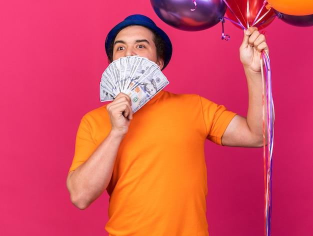 Erfreut junger mann mit partyhut mit luftballons und bedecktem gesicht mit bargeld