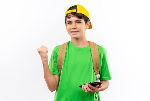 Erfreut junger schuljunge, der rucksack mit mütze trägt, die das telefon zeigt, das ja-geste isoliert auf weißer wand zeigt