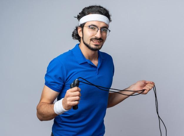 Erfreut junger sportlicher mann mit stirnband mit armband, das springseil ausstreckt