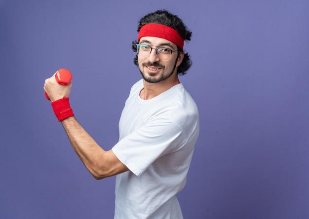 Erfreut junger sportlicher mann mit stirnband mit armband, der mit hanteln trainiert