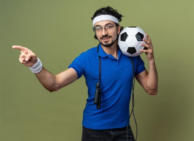 Erfreut junger sportlicher mann mit stirnband mit armband und springseil auf der schulter, der kugelpunkte an der seite hält