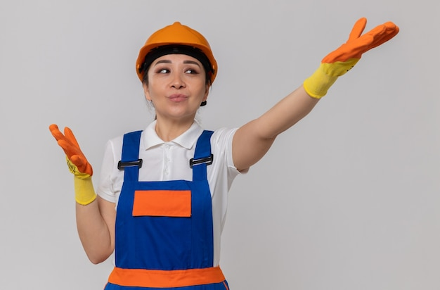 Erfreut junges asiatisches baumeistermädchen mit orangefarbenem schutzhelm und sicherheitshandschuhen, die die hände offen halten und zur seite schauen