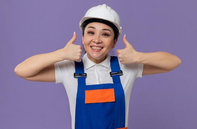 Erfreut junges asiatisches baumeistermädchen mit weißem schutzhelm, der nach oben greift