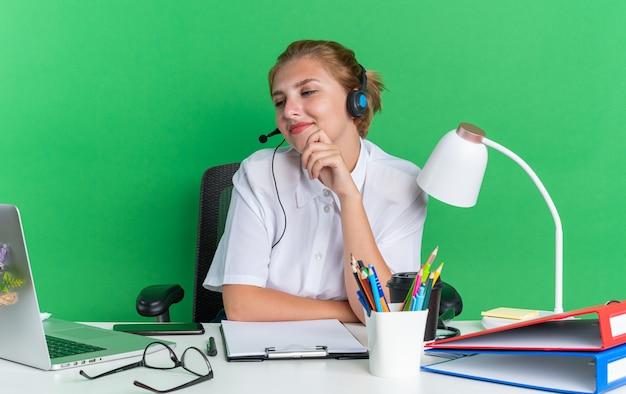 Erfreut junges blondes call-center-mädchen mit headset am schreibtisch sitzend mit arbeitswerkzeugen, die die hand am kinn halten und auf den laptop schauen, der auf grüner wand isoliert ist