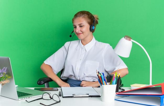 Erfreut junges blondes callcenter-mädchen mit headset am schreibtisch sitzend mit arbeitswerkzeugen, die auf den laptop schauen