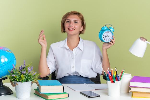 Erfreut junges blondes studentenmädchen, das am schreibtisch mit schulwerkzeugen sitzt und die hand in der luft hält und den wecker mit blick auf die kamera isoliert auf olivgrüner wand hält?