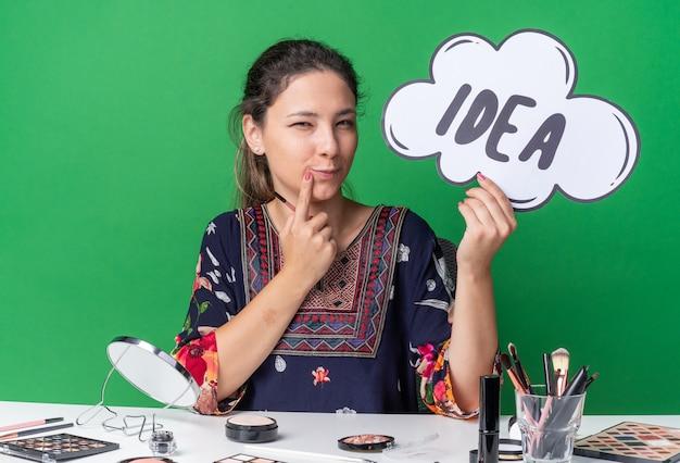 Erfreut junges brünettes mädchen, das am tisch mit make-up-werkzeugen sitzt, die ideenblase und make-up-pinsel einzeln auf grüner wand mit kopienraum halten