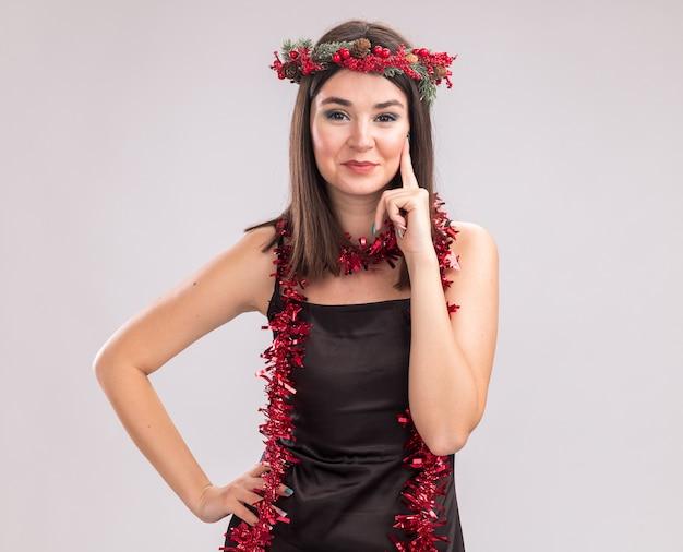 Erfreut junges hübsches kaukasisches mädchen, das weihnachtskopfkranz und lametta-girlande um den hals trägt und in die kamera schaut, die die hand auf der taille hält und das gesicht isoliert auf weißem hintergrund mit kopierraum Kostenlose Fotos