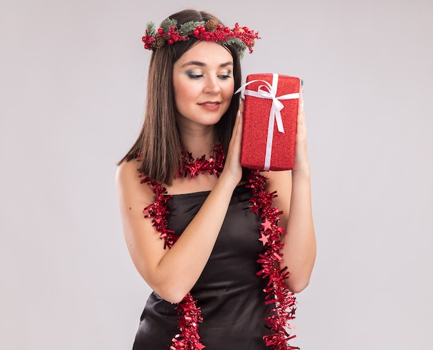 Erfreut junges hübsches kaukasisches mädchen, das weihnachtskopfkranz und lamettagirlande um den hals trägt und geschenkpaket einzeln auf weißem hintergrund mit kopienraum betrachtet