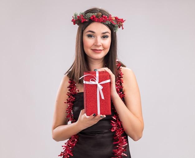 Erfreut junges hübsches kaukasisches mädchen mit weihnachtskopfkranz und lametta-girlande um den hals, das geschenkpaket hält und die kamera einzeln auf weißem hintergrund mit kopierraum betrachtet